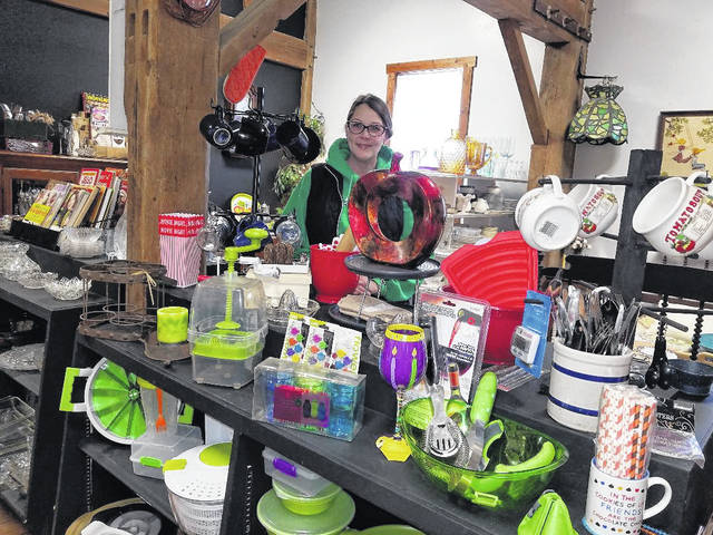 Photo by Louise Swartzwalder Love our Hero's owner Tami Oyster, before a colorful display in her store at its new home in old Pumpkin Hollow building, next to the bike trail in downtown Bellville.