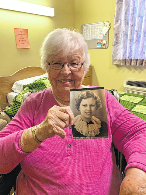 Photo by Jodi Myers Charlotte Geyer holds up her senior class photograph, which was taken in 1937. She remembers the day, saying the knitted collar she is wearing was borrowed from a friend and they both wore it for their senior pictures.