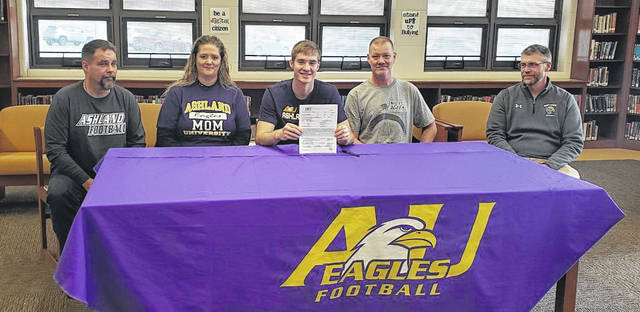 Northmor senior Blake Miller (center) holds his signed letter of intent to play football at Ashland University next fall. In the picture are (l-r) stepfather Damon Hunter, mother Jessie Hunter, Miller, father Mike Miller and Northmor football coach Scott Armrose.