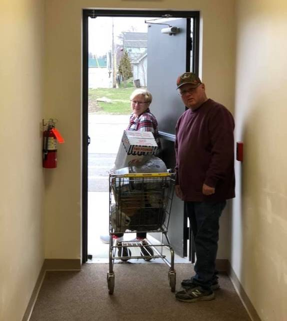 Courtesy photo After collecting an order for a client Saturday at the food pantry at St. Paul United Methodist Church in Galion, Jim and Vicki Myers are ready to deliver the goods to the client, who is waiting in the car.