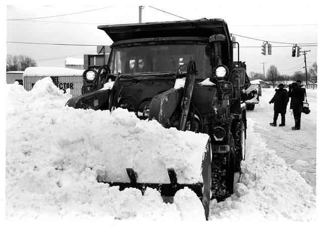 Photos from Ohio Army National Guard Historical Collections   Ohio Army National Guard engineers use small emplacement excavators, or SEEs (backhoe/front-end loader combinations), to aid snow removal in Belpre, Ohio during a snow emergency in 1994.