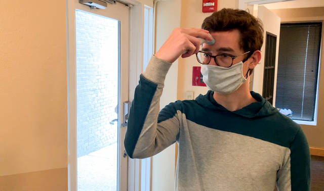 Evan Wilkerson takes his temperature upon arriving at work. As COVID-19 restrictions are lifted and businesses begin to reopen, experts at The Ohio State University Wexner Medical Center say precautions like this prevent the spread of infection and also help employees feel safe.