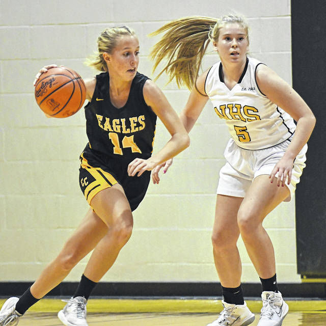 Colonel Crawford's Ally Hocker (14) drives to the middle of the floor against Northmor's Paige Caudill (5) during the season-opening ballgame for both squads on Friday, Nov. 20, 2020, at the NHS gymnasium. The Eagles outscored the Knights 27-12 in the second half and rolled to a 45-19 victory.