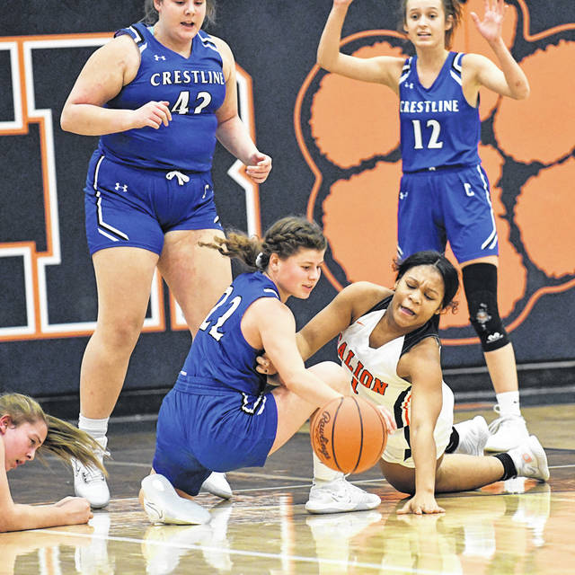 Crestline's Maddie Engler (22) and Galion's Heaven Phelps battle for a loose ball during the first half of the rivalry matchup on Tuesday, Nov. 24, 2020, at Galion High School. Lady Bulldogs Brynn Cheney (42) and Ivy Stewart (12) watch the scuffle for the ball. Crestline rallied from a 9-point deficit at the end of the third period to earn a 41-34 victory over the Tigers.
