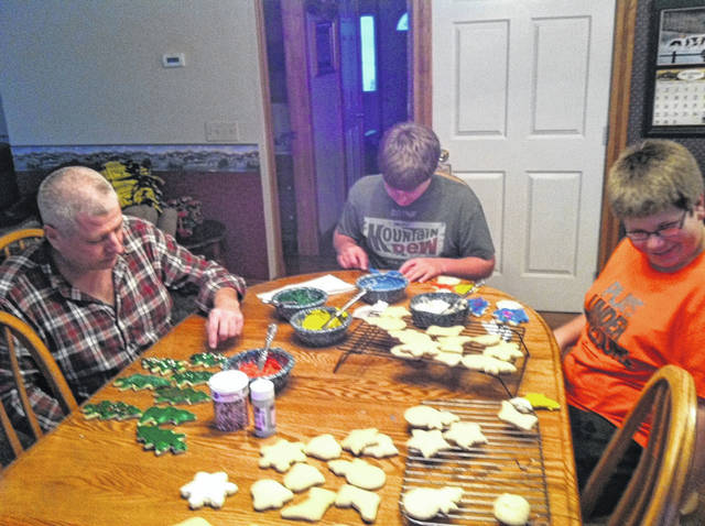 Gary Myers, left, and his sons, Shane and Travis, decorate Christmas cookies at the family table in this photo taken during the holiday season several years ago. Baking sweets for the holidays has been a tradition for mom Jodi Myers and her family for many years.