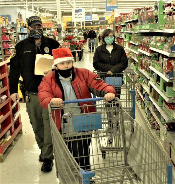 Officer Ralph Burwell of the Galion Police Department shops with Galion City Schools students Christopher Goodwin (front) and Hannah Nelson during the annual Shop with a Cop event held Thursday, Dec. 17, 2020, at Walmart in Bucyrus. Galion officers shopped with eight children this year.
