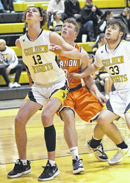 Brayden Eckels of Galion, center, battles Northmor's Kooper Keen (12) and Andrew Armrose (33) for position under the basket during the rivalry game between the Tigers and Golden Knights on Tuesday, Dec. 29, 2020, at The Castle. Northmor won the game, 48-32.
