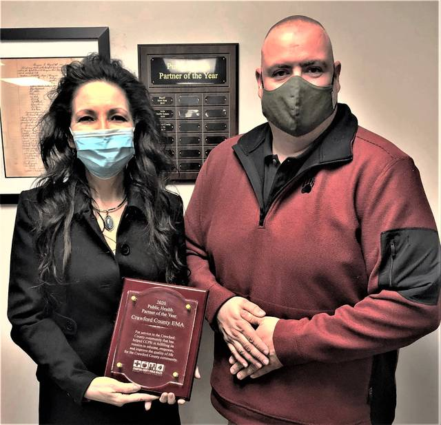 Crawford County Board of Health President Zach Wolfe, right, presents the 2020 Public Health Partner of the Year plaque to Jette Cander, Crawford County EMA Director.