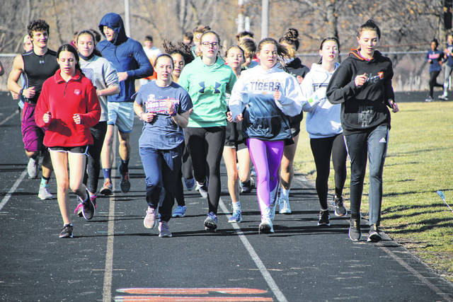 Members of the Galion High School track and field team run warm-up laps at the start of practice on Wednesday, March 3, 2021. The State of Ohio has eased restrictions on the capacity requirements for indoor and outdoor athletic events, which means more fans in the stands to watch these athletes and others around the Buckeye State this spring.