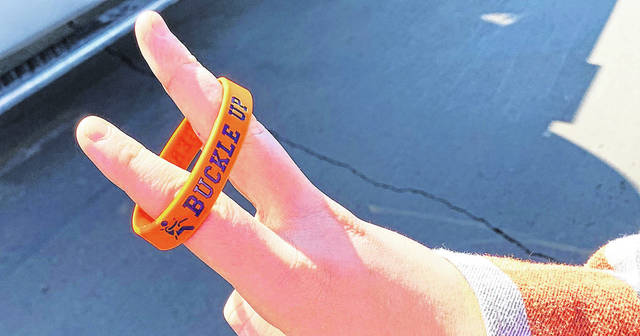 """Members of the Galion High School Family, Career, and Community Leaders of America group passed out """"Buckle Up"""" bracelets to their classmates as part of a collaborative project with Galion Police Department School Resource Officer Ralph Burwell."""