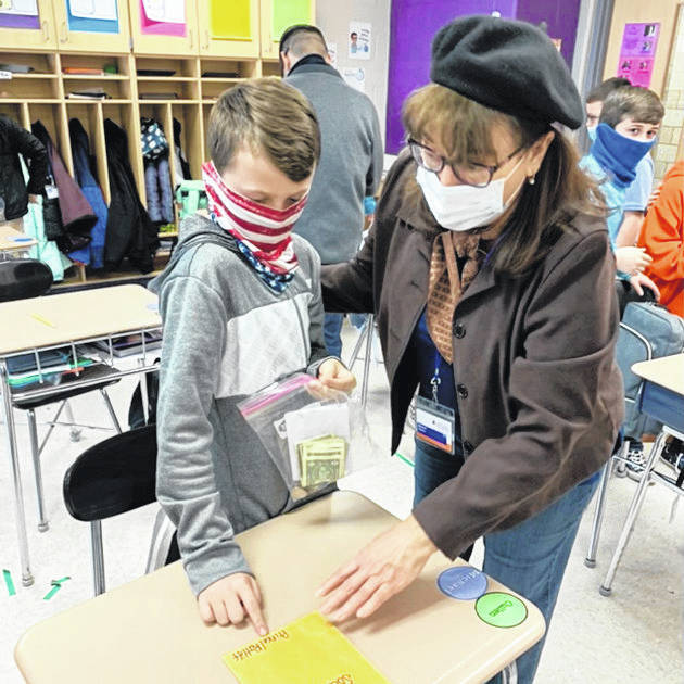 Galion City Schools Treasurer Charlene Parkinson, right, works with fifth-grade student Cullen Hart, left, to count donations and prepare a deposit for the Galion Intermediate School's fundraiser to support the Humane Society Serving Crawford County.