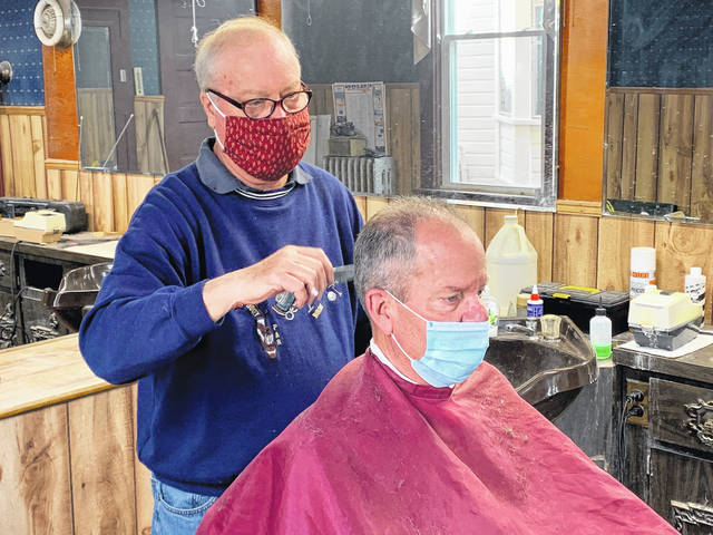 """Doug Schreck, left, trims the hair of a customer at his barber shop located at 213 South Market Street in Galion on Friday, April 30, 2021. Schreck retired this past weekend after 50 years of serving the Galion community. """"Galion is a good community. It's supported me and my family really well,"""" Schreck said."""