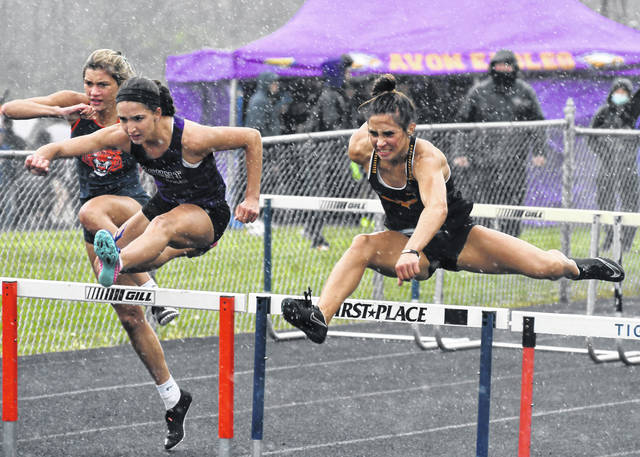 Colonel Crawford's Katie Ruffener, right, Mount Gilead's Allison Johnson, second from right, and Galion's Samantha Comer, left, battle the rain to get to the finish line in the 100-meter hurdles race on Friday, May 7, 2021, during the Galion Kiwanis Invitational track and field meet at Heise Park. Ruffener, Johnson, and Comer finished 1-2-3 in the event. Ruffener went on to win a total of three events at the meet.