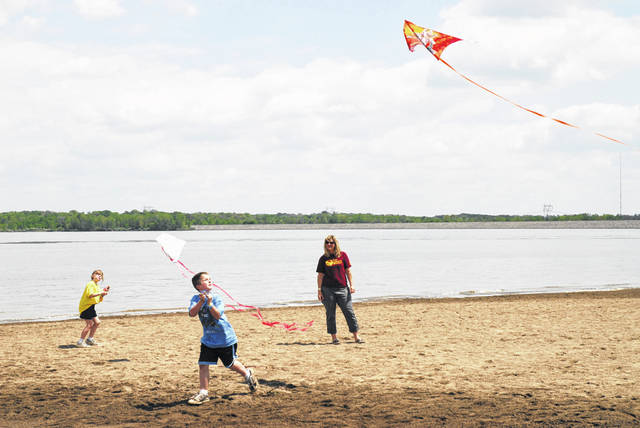 Kids are shown flying kites on the beach at Alum Creek State Park in Delaware County.