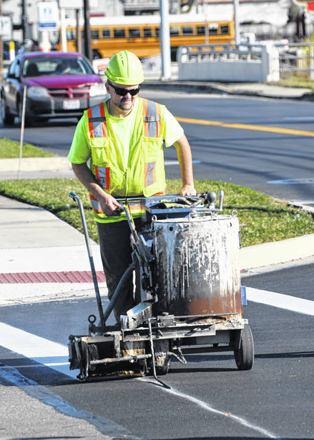 An employee of American Roadway Logistics paints lines on a crosswalk to put the finishing touches on the Harding Way paving project in this photo taken on Monday, Nov. 9, 2020. A street paving project involving 15 roadways in Galion is scheduled to begin on Monday, Aug. 2.