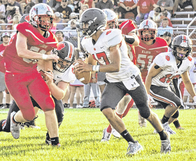 Galion quarterback Hanif Donaldson (17) looks for space to move during the Tigers 2021 season opener against Elgin on Friday, Aug. 20, 2021, in Marion. Galion won a tough contest 15-12 against the Comets. Donaldson rushed for 192 yards and a touchdown to pace the Galion offense. Galion offensive lineman Alex Griffith, lower left, throws a block on the play. Running back Sam Wegesin, right, watches Donaldson make his move.