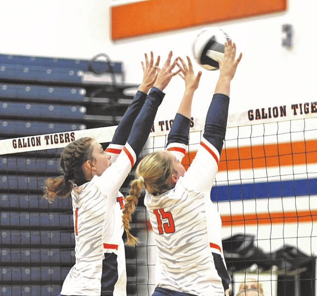 Jillian Capretta, left, and Emma Jutz extend their arms to block a shot during the Lady Tigers' match against Bellevue on Tuesday, Aug. 24, 2021. The Lady Red won a five-set thriller against Galion coming back to win the final two sets.