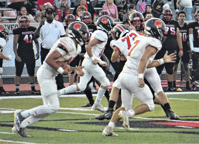 Galion running back Hanif Donaldson (left) looks for room to run behind the block of teammate Kooper McCabe (right) during the Tigers game against Marion Harding on Friday, Sept. 17, 2021, in Marion. The Presidents won the game 24-15 to snap Galion's two-game winning streak.