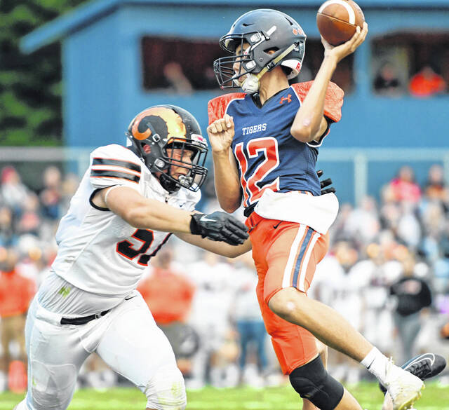 Galion quarterback Cooper Kent (12) goes airborne to attempt a pass under pressure from Upper Sandusky's Braxton Johnson during the Tigers 31-0 shutout victory on Friday, Sept. 3, 2021, at Unckrich Stadium. Kent made his first start and completed 8-of-13 passes for 68 yards and a touchdown. The Galion offense, defense, and special teams each scored a touchdown against the Rams.