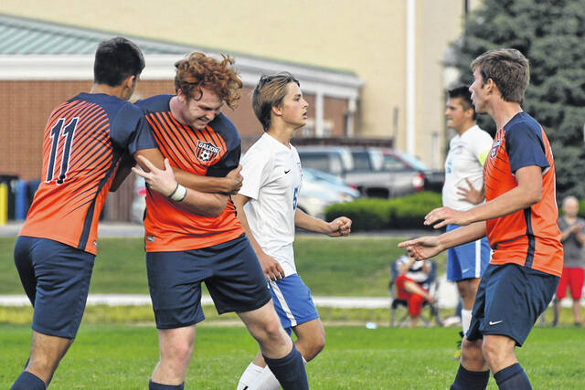 Galion players celebrate with Kennan Walker (center) after he scored what proved to be the match-winning goal against Highland on Monday, Sept. 27, 2021. Walker Frankhouse (11) had the assist on Walker's goal that gave the Tigers a 2-1 win over the Scots.