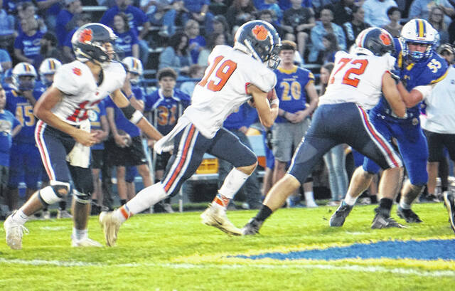 Galion's Gabe Ivy (19) takes the handoff from Cooper Kent during the Tigers game against Ontario on Friday, Oct. 8, 2021. Ivy finished with 94 yards rushing and a touchdown to help pace Galion to a 7-6 win against the Warriors. Offensive lineman Mitchell Young (72) helps pave the way for Ivy on the play.