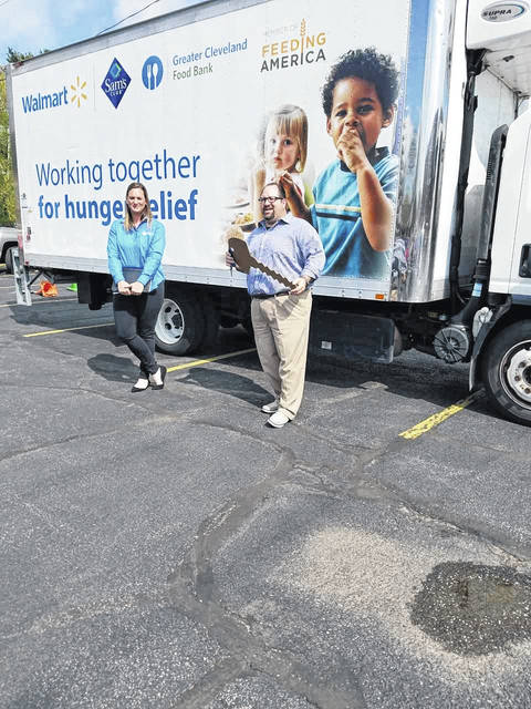 Jess Morgan, of the Greater Cleveland Food Bank, presents a giant key to Matt Merendino, with Bellville Neighborhood Outreach Center (BNOC). The arrival of a new refrigerated truck was celebrated in the back parking lot behind BNOC offices. Louise Swartzwalder | Bellville Star
