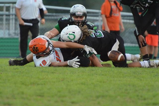 North Union's Trevyn Feasel and Clear Fork's Trevon Trammell and James Watts scramble for a first-half fumble Friday night. The Colts won their fourth game in a row, 42-14, after a close first half.