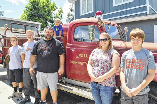 The Boeriu family poses in front of an old fire truck from Ashley, Ohio. Aiden Boeriu, 13, left, Dominic Boeriu, 15, Erik Boeriu, his wife Aimee Boeriu and Alex Boeriu, 13, stand for the photo, while Nikolas Boeriu, 5, sits on top of the fire truck. Erik is organizing the Fourth of July parade this year after the Delaware County Farm Bureau decided to no longer organize the function.