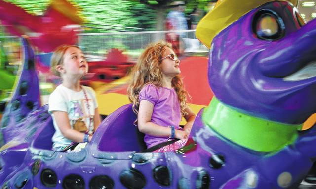 The 91-degree summer weather Friday didn't keep families from walking down William Street to the annual St. Mary Festival. The heat didn't seem to bother either Isabella Cook (left) or Skyler Hatten (right) as they took a spin on a crocodile's back not long after the festival opened at 5 p.m. Friday. The festival will be open from 5 p.m. to midnight Saturday at 82 E. William St. in Delaware.