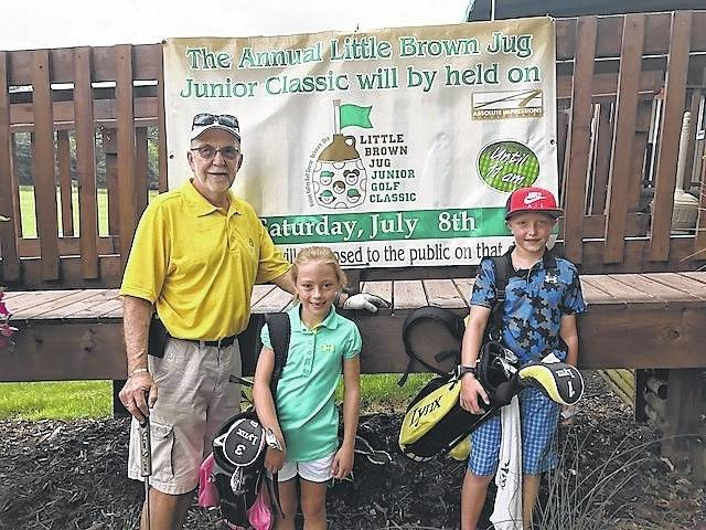 Ed Schlote, left, and his grandchildren Laney Miller, 7, and Jaxen Miller, 9, practiced at Hidden Valley Golf Course this month. Schlote is the event coordinator for the 42nd Little Brown Jug Junior Golf Classic.