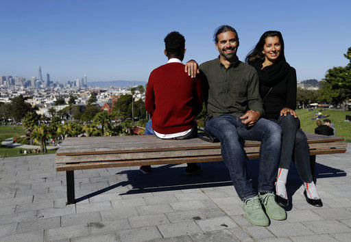 Mike Gougherty, center, and Julie Rajagopal, right, pose for photos with their 16-year-old foster child from Eritrea at Dolores Park in San Francisco. When their 16-year-old foster child landed in March, he was among the last refugee foster children to make it into the U.S. Trump administration travel bans declared to block terrorists also are halting a small, three-decade-old program bringing orphan refugee children to waiting foster families in the United States.