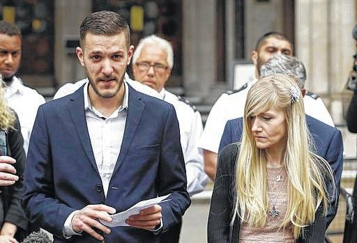 Chris Gard, the father of critically ill baby Charlie Gard finishes reading a statement next to mother Connie Yates, right, at the end of their case on Monday at the High Court in London. The parents of critically ill baby Charlie Gard dropped their legal bid Monday to send him to the United States for an experimental treatment after new medical tests showed that the window of opportunity to help him had closed.