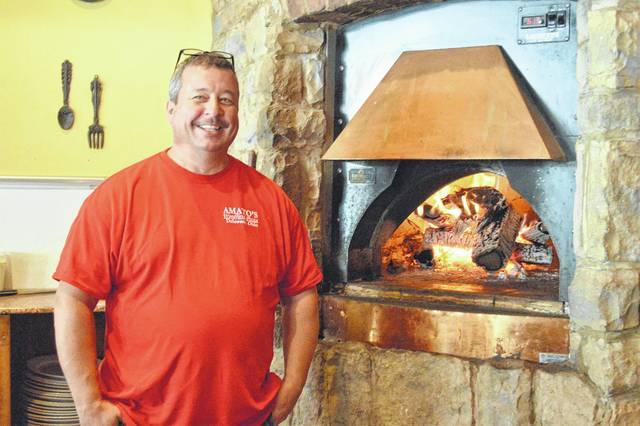 Craig Johnson poses next to the fireplace at Amato's Woodfired Pizza, 6 S. Sandusky St., in downtown Delaware. He and fellow co-owner Brad Hampu plan to open their third location in Marion by early 2018.