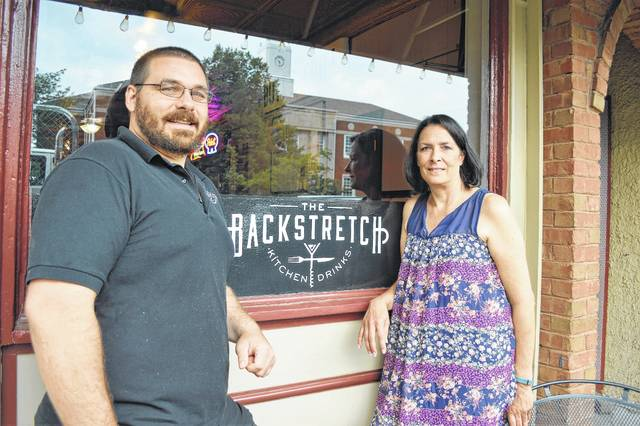 Kyle Meyer, left, and his mother, Joanne Meyer, pose outside their restaurant and bar at 14 S. Sandusky St. in downtown Delaware. The bar celebrates 35 years of being known as the Backstretch.