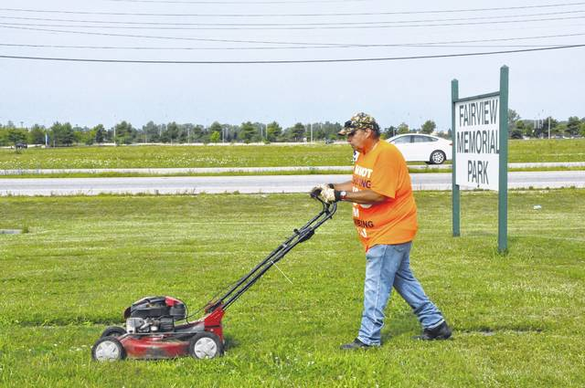 Paul O'Bryan, a Delaware resident and one of the volunteers who has been mowing Fairview Memorial Park since it's owners were indicted in February, mows the cemetery Thursday morning.