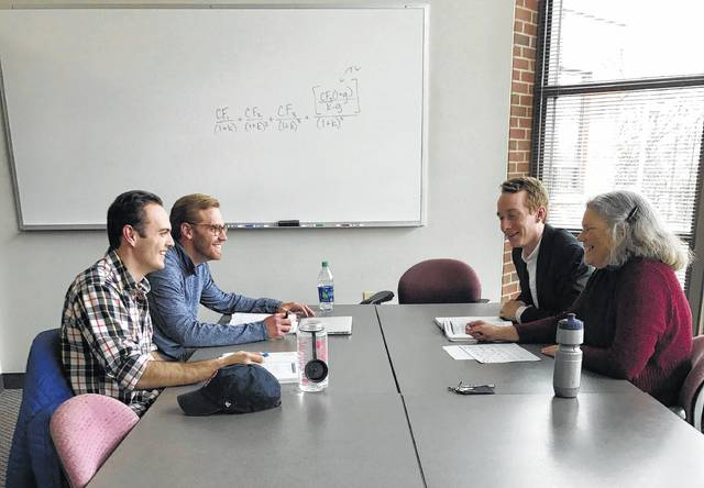 Ohio Wesleyan students J. Graham Littlehale (from left), Jamie Litzler, and Chris Brinich study for the Level 1 Chartered Financial Analyst (CFA) exam with help from economics professor Barbara MacLeod.