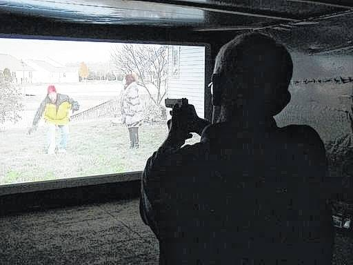 Mark Tulloch, of Kettering takes aim in a firearms training simulator Wednesday at the Clark County Fair in Springfield. The county sheriff rented the simulator to offer as a free exhibit, hoping it will help the public better understand how quickly officers must decide whether to use lethal force.