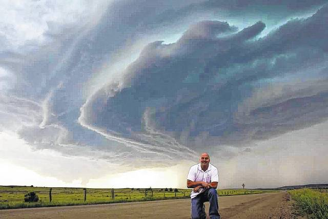 The first rule of storm chasing is, hop out of the vehicle, get the photos, and videos because that is what people do, said storm chaser Mickey Smith. In the photo, Smith is posed in front of a storm from a chase in Hulet, Wyoming in June of 2104.