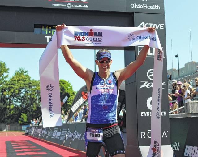 Buffalo resident Jonathan Bottoms celebrates after crossing the finish line inside Selby Stadium during Sunday's IRONMAN 70.3 Ohio.