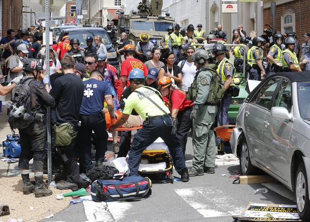 Rescue personnel help injured people after a car ran into a large group of protesters after a white nationalist rally Saturday in Charlottesville, Va. The nationalists were holding the rally to protest plans by the city of Charlottesville to remove a statue of Confederate Gen. Robert E. Lee. There were several hundred protesters marching in a long line when the car drove into a group of them.