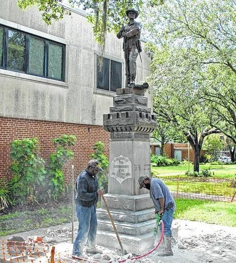 Workers begin removing a Confederate statue Monday in Gainesville, Fla. The statue is being returned to the local chapter of the United Daughters of the Confederacy, which erected the bronze statue in 1904. County officials said they did not know where the statue would be going.
