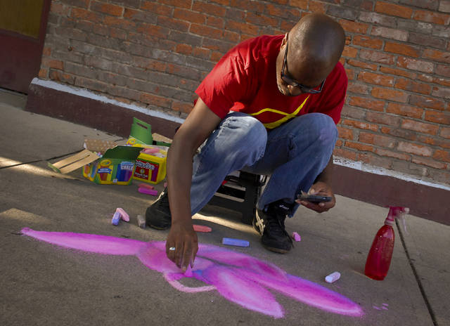 Settling into a place with lighter foot traffic along William Street next to Barley Hopsters, Myke Flournoy sketches a flower for the Main Street Delaware First Friday chalk art contest. Flournoy said he has been creating art ever since he can remember and the event was the second time he has entered the First Friday contest. July's First Friday chalk art theme was postponed due to a heavy downpour of rain and rescheduled for the First Friday in August.
