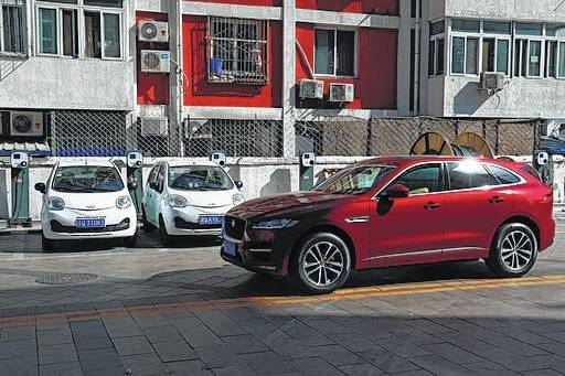 An SUV drives past electric cars parked at a charging station outside a residential building in Beijing. Momentum is building worldwide for electric cars thanks to rising government fuel economy standards and climate concerns. Automakers are jumping on board. But selling those cars will be difficult unless the world builds more charging stations.
