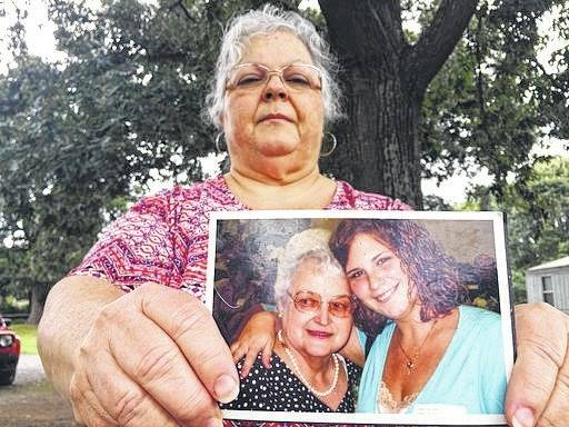 Susan Bro, the mother of Heather Heyer, holds a photo of Bro's mother and her daughter on Monday in Charlottesville, Va. Heyer was killed Saturday when police say a man plowed his car into a group of demonstrators protesting the white nationalist rally. Bro said that she is going to bare her soul to fight for the cause that her daughter died for.