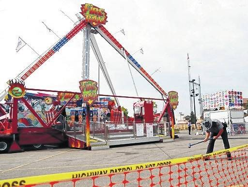"An Ohio State Highway Patrol trooper removes a ground spike in front of the fire ball ride at the Ohio State Fair in Columbus. The Dutch manufacturer of a thrill ride that broke apart and killed an 18-year-old man at the Ohio State Fair says excessive corrosion on a support beam led to a ""catastrophic failure."" A statement on KMG's website dated Friday, Aug. 4, says the company officials visited the accident site and conducted metallurgical tests."