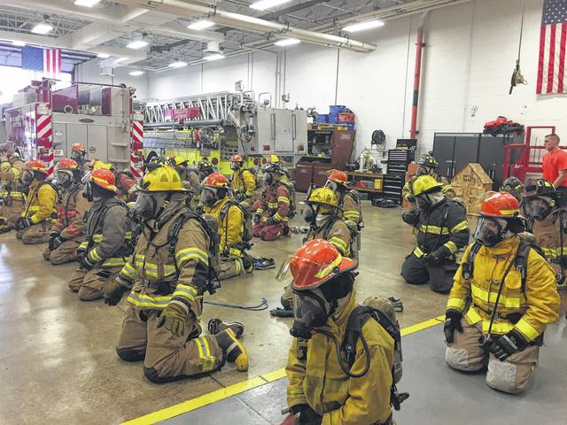 Trainees in the DACC adult fire course kneel after gearing up as quickly and efficiently as possible. Trainees did extra physical training for every second it took to get ready after the mandatory one minute and 30 seconds gear-up time had elapsed.