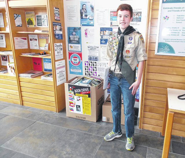 Heber Fuller, a freshman at Olentangy Orange High School, stands beside a book drive collection box at the Delaware County District Library Orange Branch, 7171 Gooding Blvd., Delaware. Fuller is collecting books for an elementary school in Texas that was ravaged by floodwaters from Hurricane Harvey.