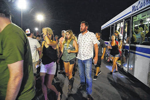 People arrive to Thomas & Mack Center via bus early Monday after hiding inside the Sands Corporation plane hangar after a mass shooting in which dozens were killed at the Route 91 Harvest country festival in Las Vegas.