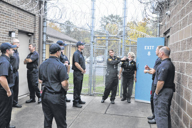 Assistant Jail Director Jessica Jackson shows firefighters from the City of Delaware one of the exits used to transport prisoners to the recreation yard. Firefighters asked questions about how the doors open and which routes would be quickest and most efficient during an emergency.