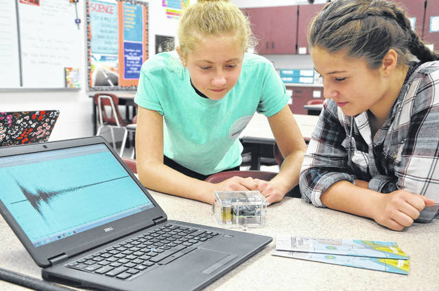 Eighth graders Eliza Riggs and Grace Goodroe examine a demonstration seismograph in class at Dempsey Middle School Wednesday. The waveform of seismic activity can be seen on the laptop next to the seismograph.